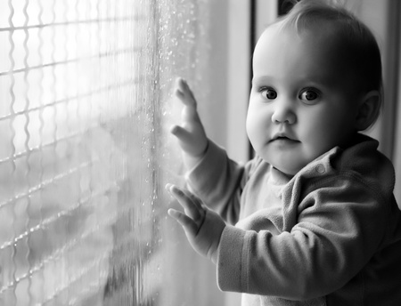 little girl looking at raindrops on the window Stock Photo - 12672355