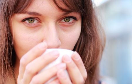 young girl with a cup of coffee  Focus on the eyes photo