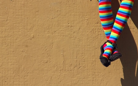 legs crossed at knee: female feet in colorful socks on the background of a gray wall  Stock Photo