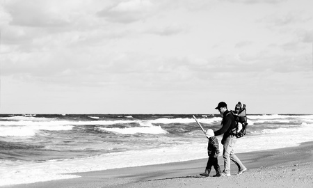Dad with a small child walking on a winter beach  photo