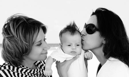 amor gay: dos hermosas chicas con un beb� en la playa