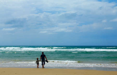 Father and son on the beach in spring time photo