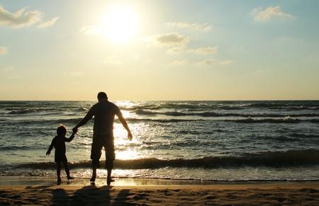 dia soleado: Padre e hijo en el mar, mirando la puesta del sol Foto de archivo