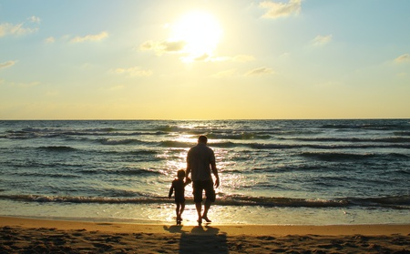 Father and son at sea watching the sunset Stock fotó