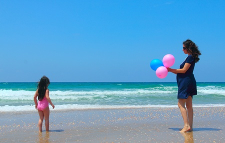 Madre embarazada con la hija en la playa con globos photo