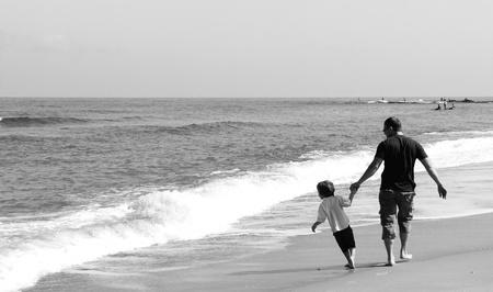 father and son playing together on the beach photo