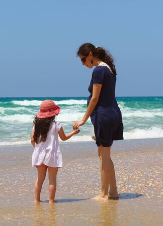 Pregnant mother with daughter on the beach photo