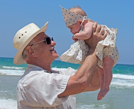 granddaughters: happy grandpa is holding a little granddaughter  Background - the sea  Stock Photo
