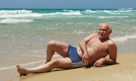 bald man: 60 años de edad, hombre que yacía en la arena en la playa
