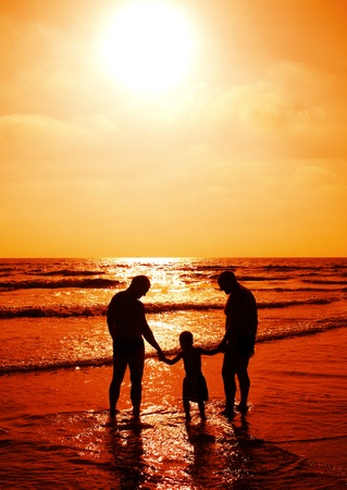 child with his father and grandfather watching sunset photo
