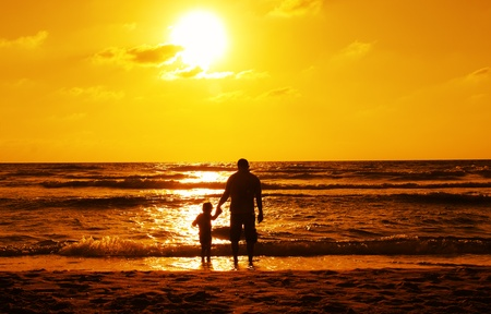 silhouettes of father and son on sunset  photo