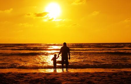 siluetas de padre e hijo en la puesta de sol Foto de archivo