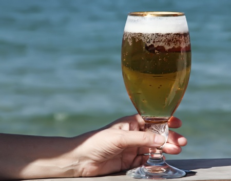 glass of blond beer on sea background  photo