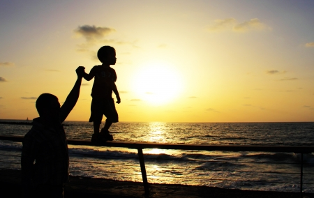 silhouettes of father and son on sunset sea background  Stock Photo - 12694357