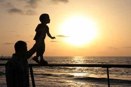 silhouettes of father and son on sunset sea background  photo