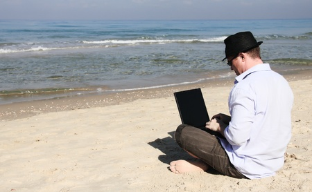 one young man only: Young man sitting on the beach with laptop  Stock Photo