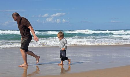 Father playing with his son at beach  photo
