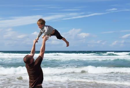 Happy father and son on the beach photo