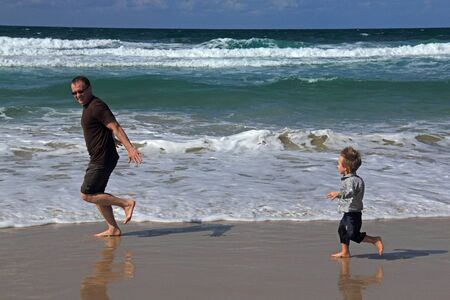 Dad and son playing on the sea  Autumn sea, strong waves, sharp colors  photo