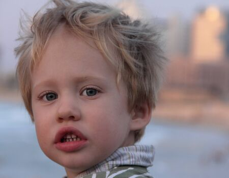 Portrait of a 3-year-old boy at sunset photo