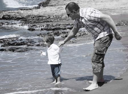 nalatenschap: De vader houdt de hand van 2-jaar oude zoon. Zwart-wit fotografie Stockfoto