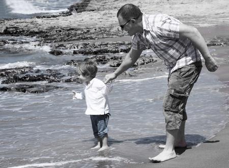 The father holds the hand of 2-year-old son. Black and white photography