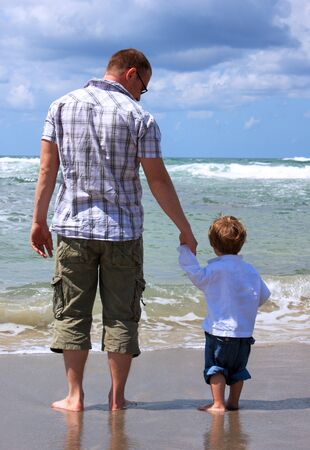 Father and son look at the sea photo