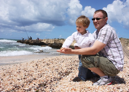 Father and son throwing shells into the sea photo