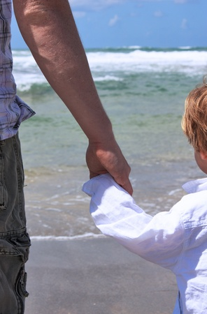 father holds the hand of his 2-year-old son photo