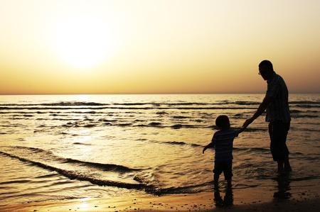 apoyo familiar: ni�o con su padre en el mar Atardecer Foto de archivo
