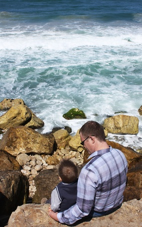 Father and son sitting on a rock and looking at the sea photo
