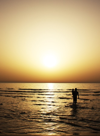 Father and son at sunset on the sea photo