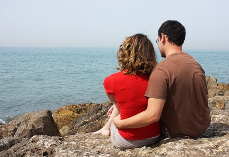 happy young couple looking at the sea photo