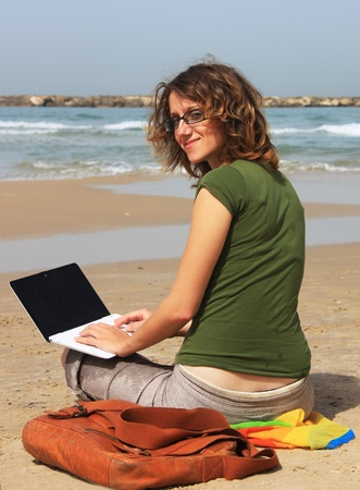 girl sitting on the beach with a small white laptop photo