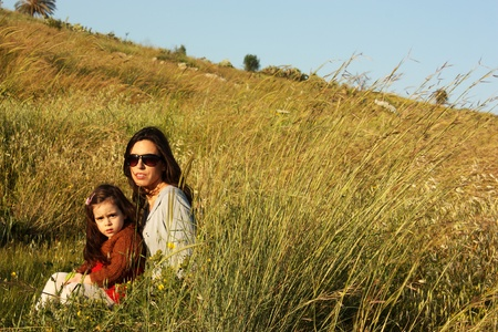 Young mother and daughter sitting on the grass  Sunset  photo
