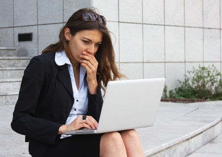 Business woman sitting on the steps with notebooks and monitors the exchange photo
