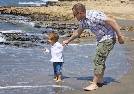 father and son playing on the beach photo