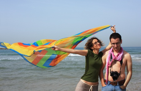 Young people on the beach with a bright colored scarf photo