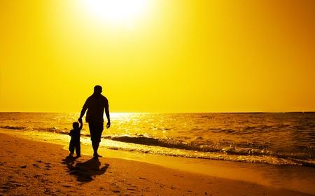 otec: Táta a dítě na pláži při západu slunce na