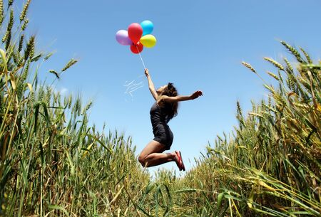 Young woman holding colorful balloons and flying over a meadow photo