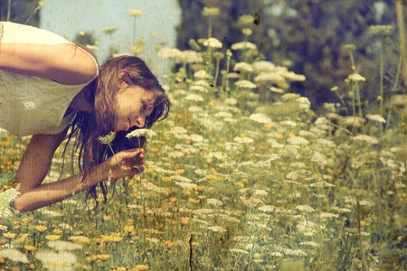 Beautiful girl smells spring flowers  Photo in old color image style  photo