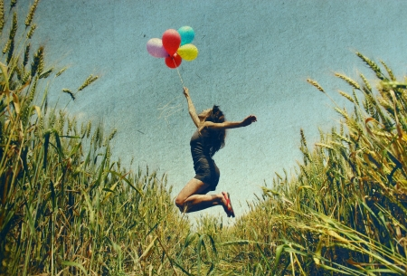 Young woman holding colorful balloons and flying over a meadow   Photo in old color image style