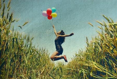 Jeune femme tenant des ballons colorés et de survoler une photo prairie dans le style ancien couleur de l'image