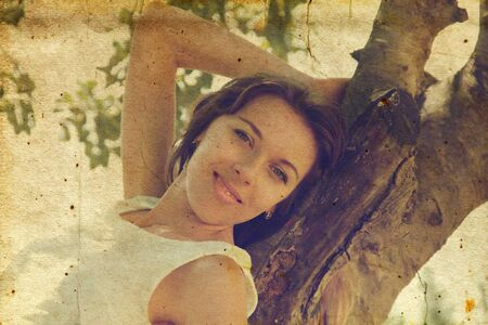 Beautiful girl in white dress sitting on the tree  Photo in old image style  photo