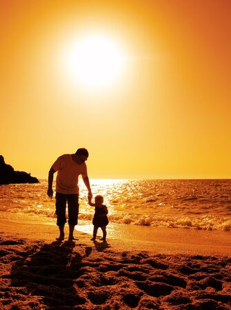 father and daughter playing on the beach at sunset Stock Photo - 13900652