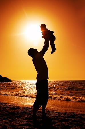 dia soleado: padre e hija jugando en la playa al atardecer