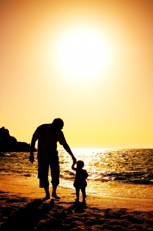 father and son holding hands: father and daughter playing on the beach at sunset Stock Photo