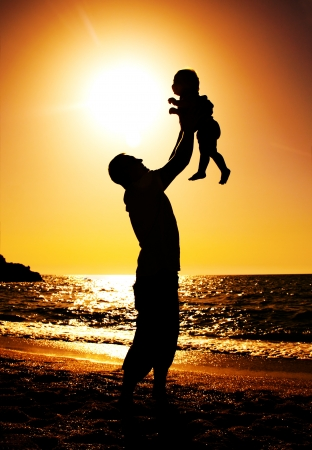 father and daughter playing on the beach at sunset Stock Photo - 13877500
