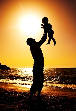 padre e hija: padre e hija jugando en la playa al atardecer