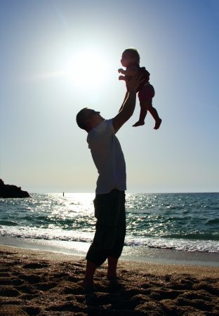 father and daughter playing on the beach at sunset Stock fotó